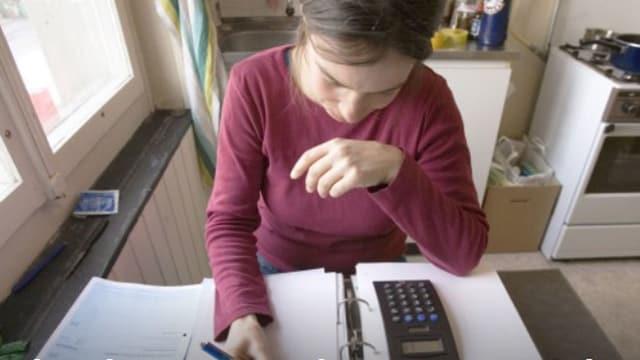 Eine Frau berechnet ihre Krankenkasse.