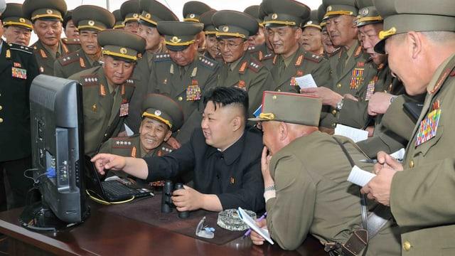 Kim Jong Un zeigt Funktionären etwas auf einem Computer-Bildschirm.