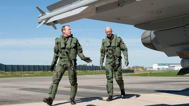 Zwei schwedische Kampfjetpiloten vor einem Kampfjet.