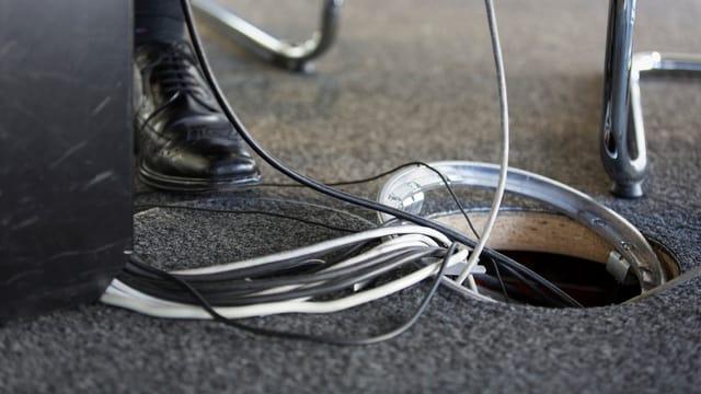 Ein Loch im Boden mit Kabeln.