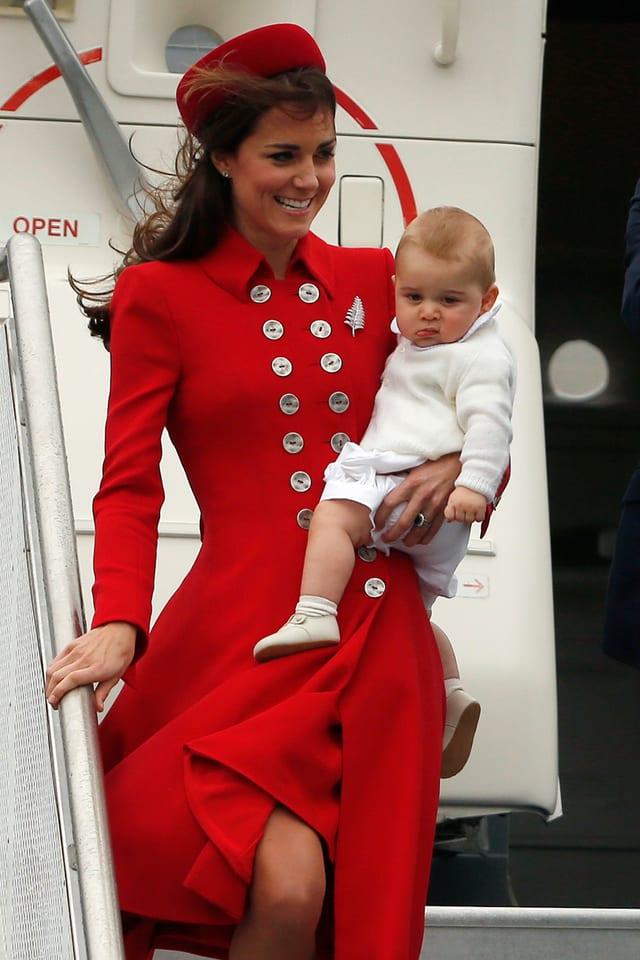 Frau mit rotem Kleid und Kind im Arm