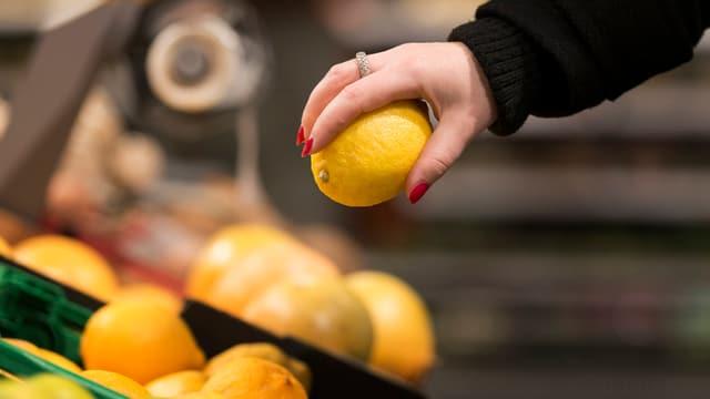 Eine Hand greift nach einer Zitrone in einem Supermarkt.