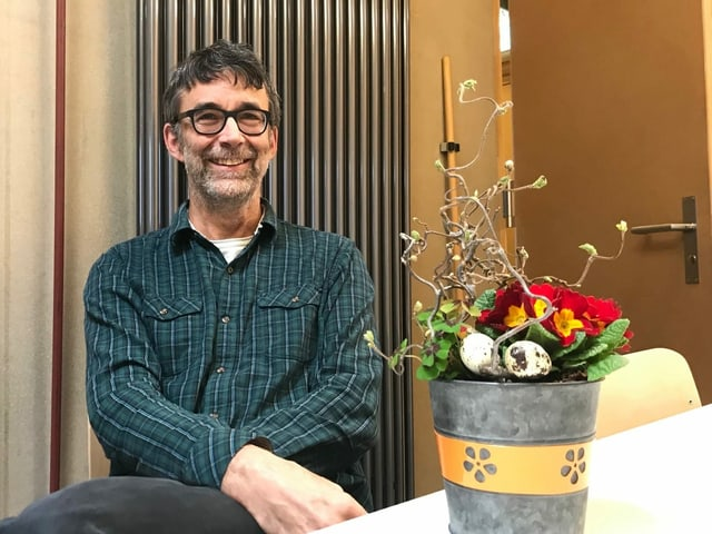 Dominik Egli sitzt auf einem Stuhl. Auf dem Tisch vor ihm steht ein Blumentopf