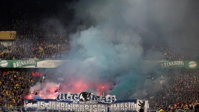 Pyro-Technik und Nebel auf einer Stadiontribüne.