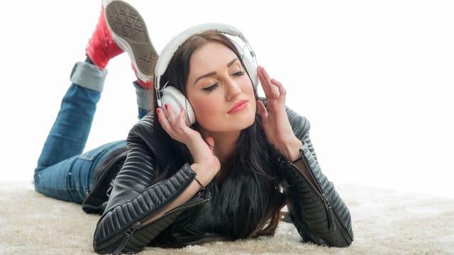 Eine Frau liegt auf dem Boden, hört über Kopfhörer Musik und geniesst.