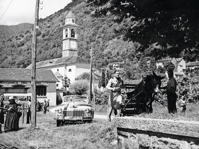 Filmszene in Schwarzweiss: Tessiner Dorf mit einer steinernen Kirche. Ein Mann rennt neben einem Pferdewagen. Im Hintergund ein altmodisches Auto mit offenem Verdeck.
