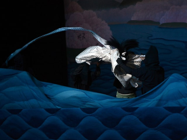 Eine japanische Theaterpuppe, die mit einem langen Schweiz über die Bühne fliegt.