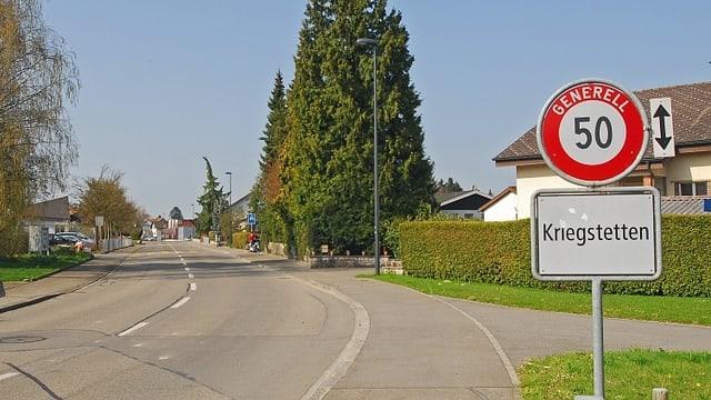 Ortsschild von Kriegstetten neben unbefahrener Strasse.