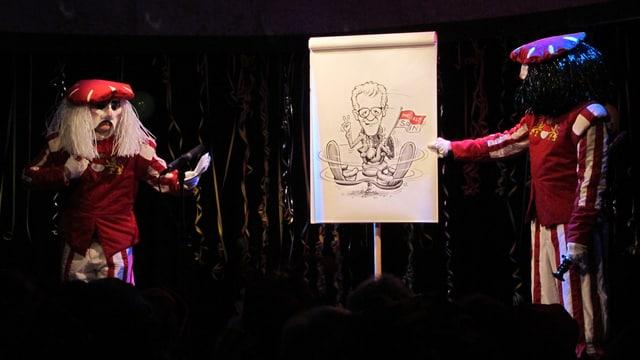 Männer in rot-weissen Kleidern, in der Mitte ein Plakat.