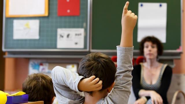 Symbolbild: Eine Lehrerin sitzt vor der Wandtafel, ein Schüler streckt die Hand hoch.