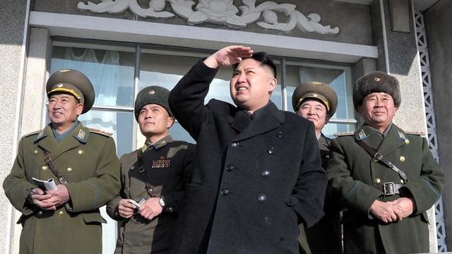 Nordkoreas Machthaber Kim Jong Un schaut nach oben. Neben ihm stehen Militärangehörige.