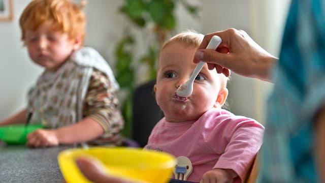 Eine Mutter füttert ihr Baby mit Brei.