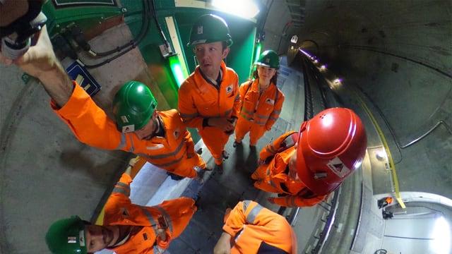 Männer und Frau, in orangen Arbeiter-Schutzanzügen und mit Helm, Fish-Eye-mässig verzerrt weil von oben fotografiert.