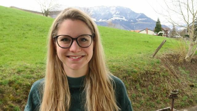 Eine blonde Frau mit Brille vor einer grünen Wiese.