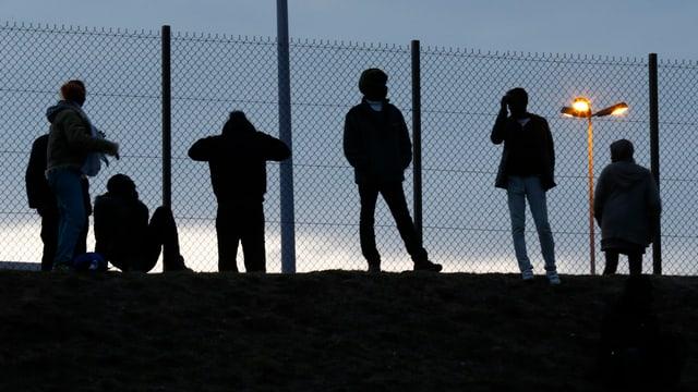 Flüchtlinge stehen an einem Zaun.