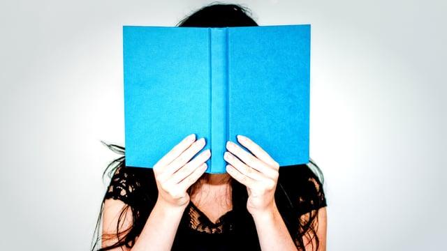 Eine Frau hält ein hellblaues Buch.