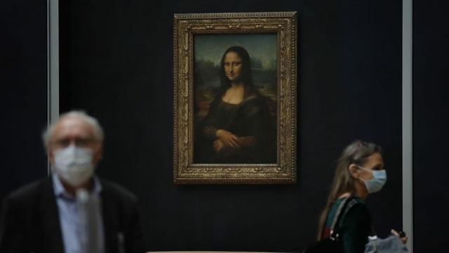 Menschen mit Schutzmasken vor dem Bild der Mona Lisa.