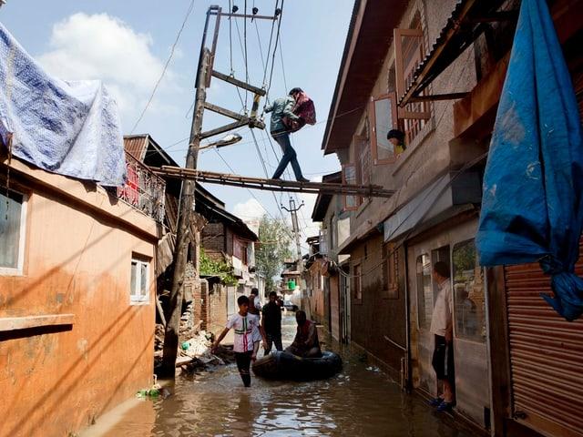 Mann auf einer Leiter über dem Hochwasser