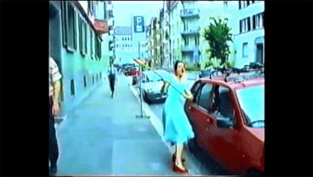 Frau schlägt Autoscheibe mit Blume ein.