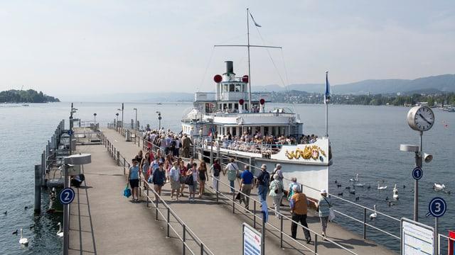Ein Raddampfer auf dem Zürichsee legt am Steg beim Bürkliplatz an.