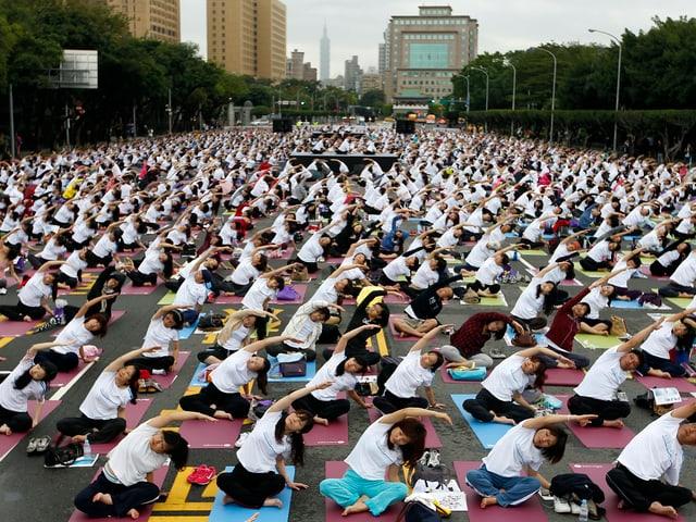 Tausende Menschen bei einer Yoga-Übung im Freien
