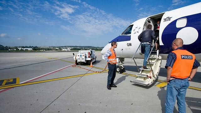 Ein Mann steigt in ein Flugzeug, beobachtet von zwei Polizisten.