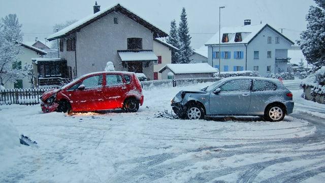 Zwei beschädigte Autos nach einem Unfall auf der schneebedeckten Strasse.