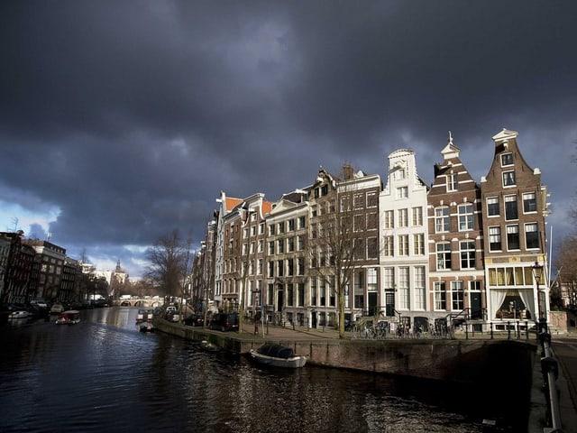 Die Amsterdamer Keizersgracht vor grauem Himmel.