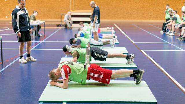 Mehrere junge Männer beim sportlichen Test in der Turnhalle.