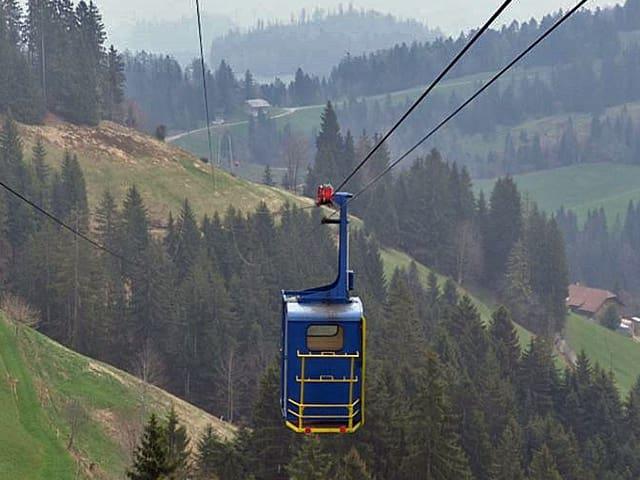 Eine blaue Seilbahn-Gondel schwebt über der Landschaft