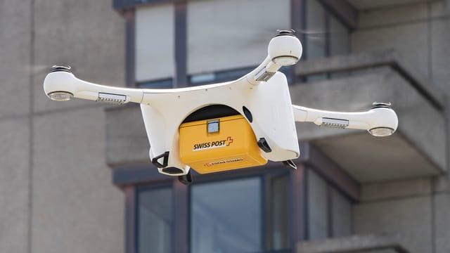 ina drona en l'aria cun in pachet da la Posta Svizra