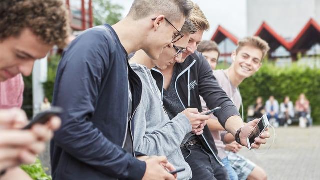Eine Gruppe Jugendlicher tauscht auf einem Pausenplatz Informationen auf ihren Handys aus.