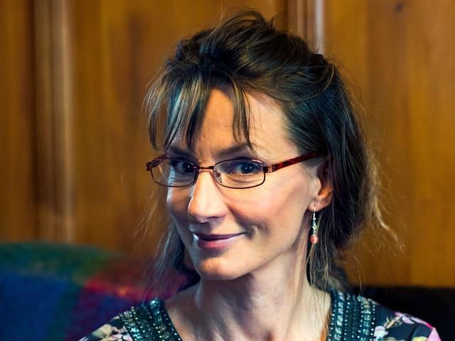 Eine Frau mit blumigem Oberteil und Brille.