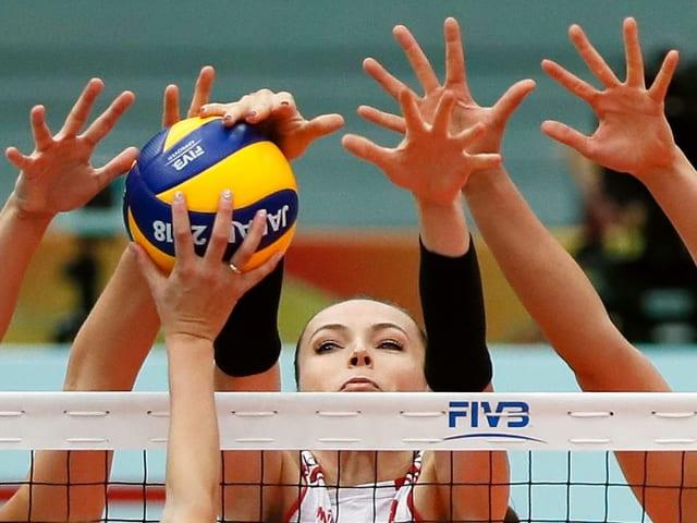 Viele Hände greifen nach einem Block-Ball am Netz.