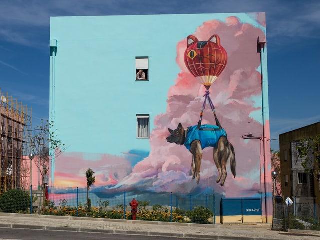 An einer Hausfassade wurde ein Hund gemalt, der an einem Ballon fliegt.