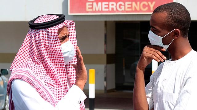 Zwei Männer mit Atemschutzmaske vor einem Krankenhaus in Damman, Saudiarabien.