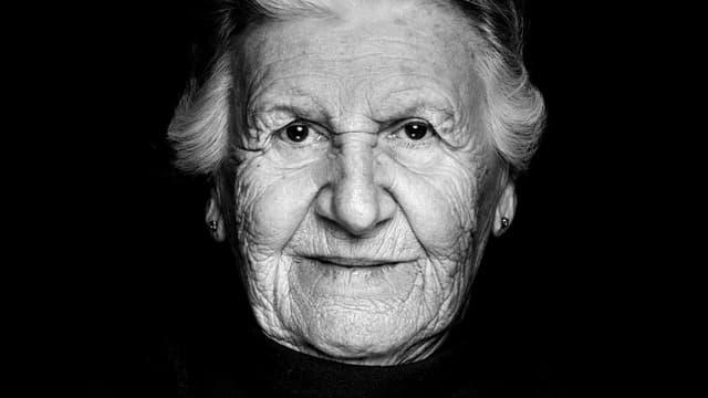 Eine ältere Frau blick in die Kamera.