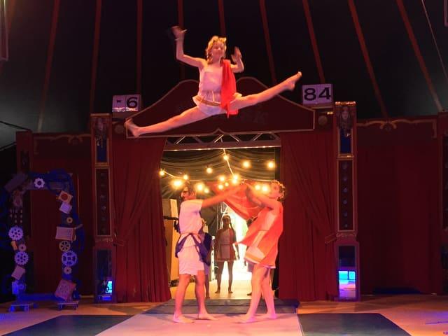 Ein Akrobat macht in der Luft den Spagat.