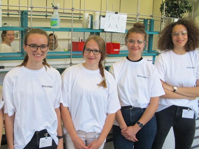 Vier Jugendliche stehen im Labor und posieren fürs Foto.