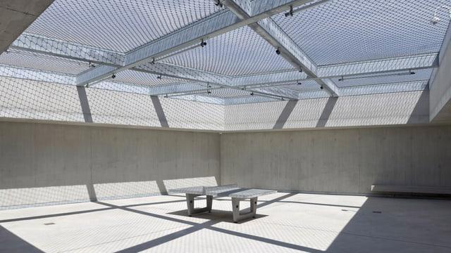 Ein kahler Raum mit einem Tisch in der Mitte und einer vergitterten Öffnung nach oben