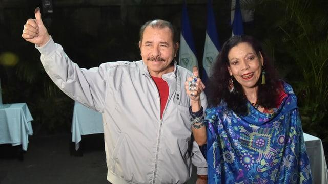 Ortega und seine Frau halten nach der Stimmabgabe den gefärbten Daumen hoch.