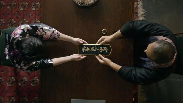 Zwei Menschen von oben gesehen, deren Hände eine Tafel mit japanischen Schriftzeichen halten.
