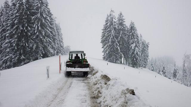 Traktor fährt auf einem schneebedeckten Weg.