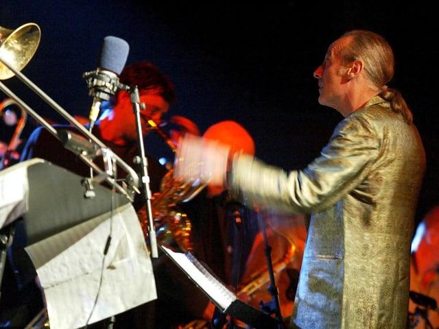 Mathias Rüegg steht vor Musikern und dirigiert