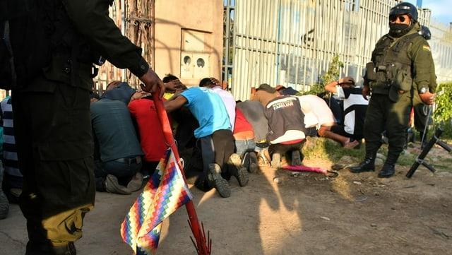 Kniende Menschen mit Händen über Kopf. Daneben Polizei.