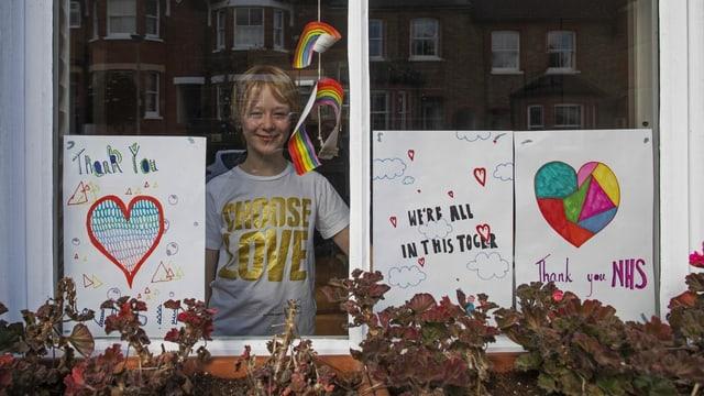Kind steht hinter verschlossenem Fenster in Corona-Zeiten in Grossbritannien