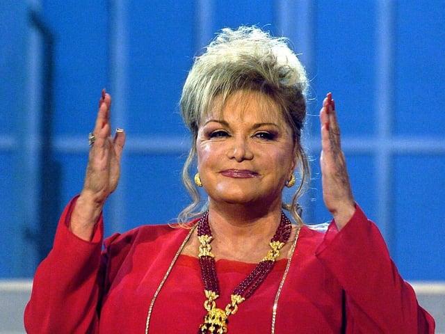 Eine Sängerin im roten Kleid während eines Fernsehauftritts.
