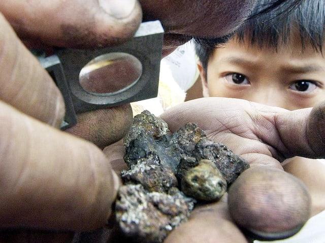 Ein Mann schaut mit einer Lupe einen verdreckten Klumpen nach Gold ab. Im Hintergrund schaut ein Kind auf das Gestein.
