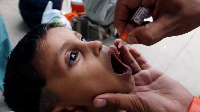 In uffant che survign daguts da la vaccinaziun en bucca.