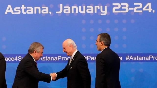 Der UNO-Gesandte De Mistura (M) schüttelt dem russischen Spezialgesandten Lawrentiew die Hand.